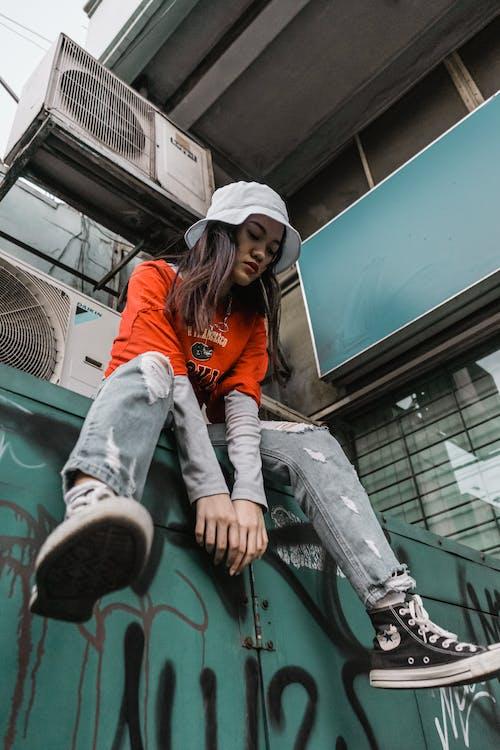 Woman in Orange Hoodie and Gray Denim Jeans Sitting on Green Metal Frame
