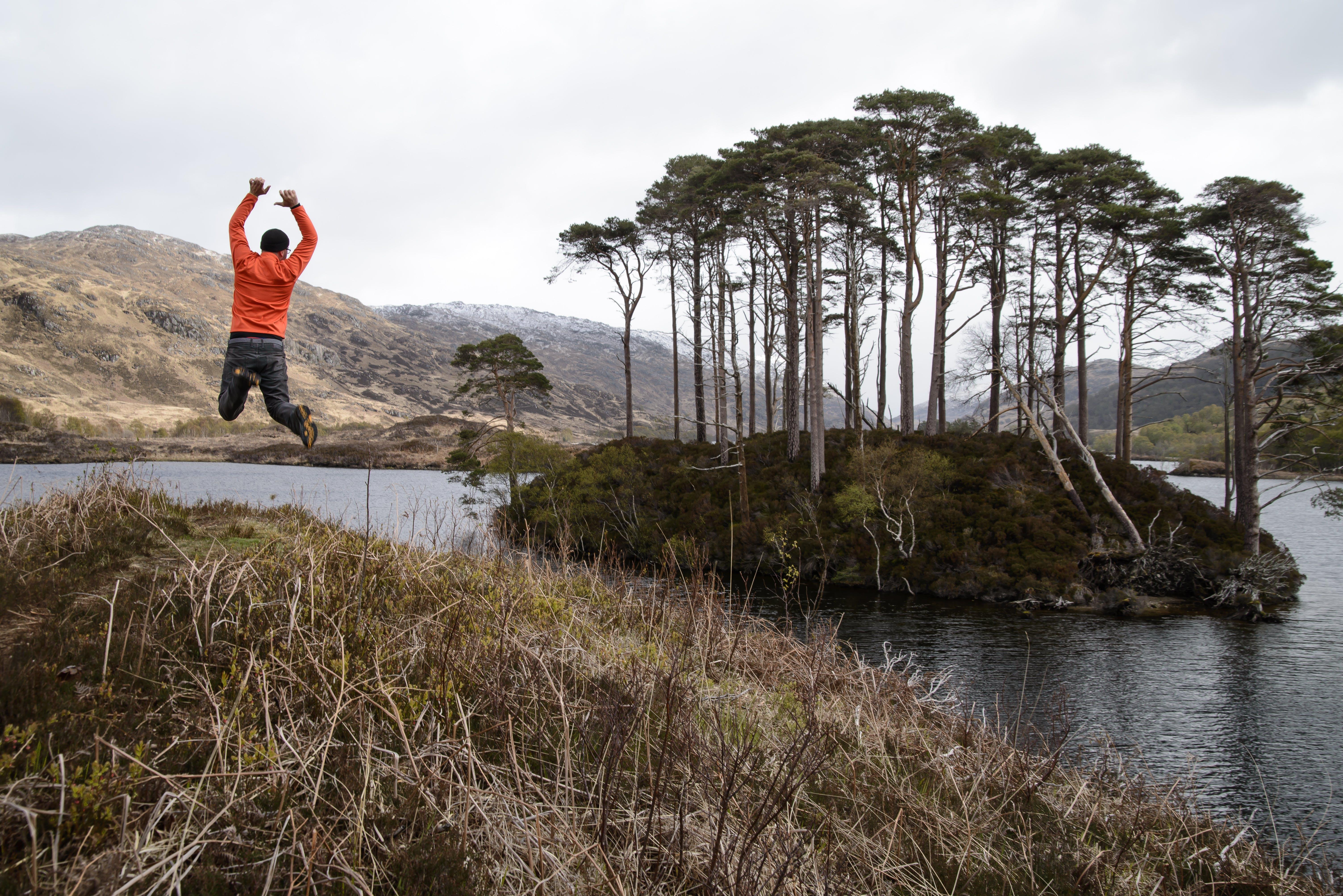 Man in Orange Long-sleeved Shirt Jumping on Lake Near Tall Trees at Daytime