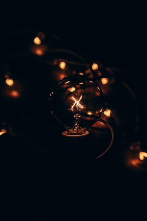 Shining glass lamp illuminating dark room in flat