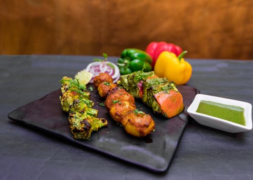 Assorted bright grilled vegetables with savory green sauce in restaurant