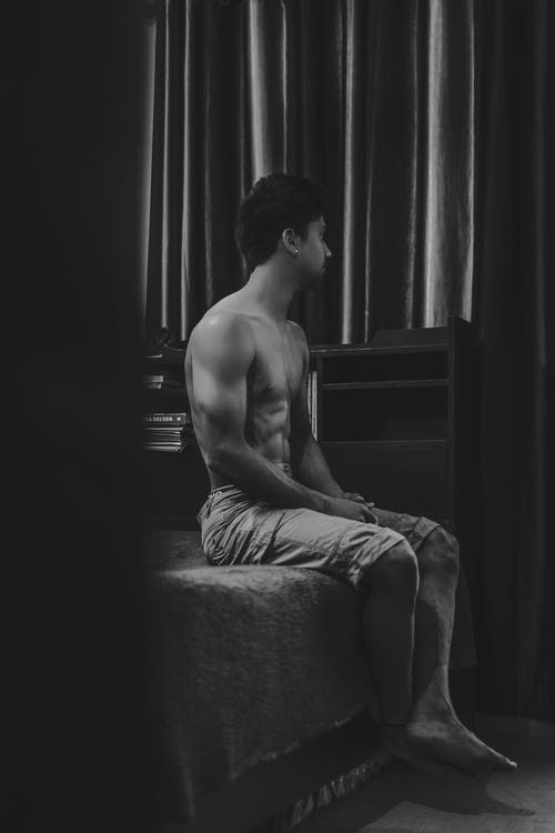 Grayscale Photo Of a  Topless Man Sitting on Bed