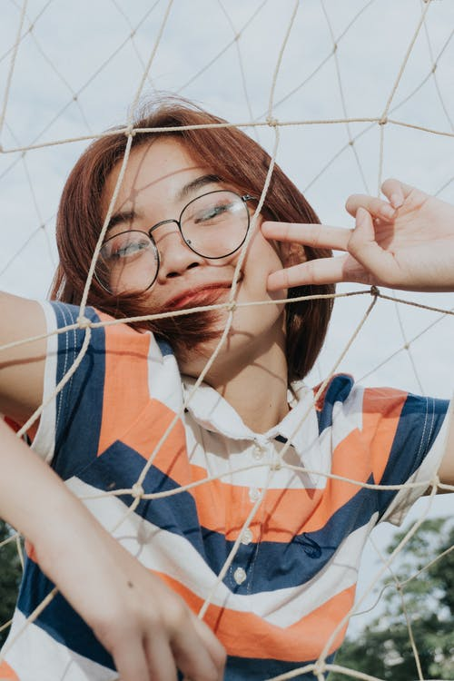 From below of slim cheerful young ethnic female in striped t shirt and eyeglasses demonstrating victory gesture while standing near grid fence in daylight and looking at camera