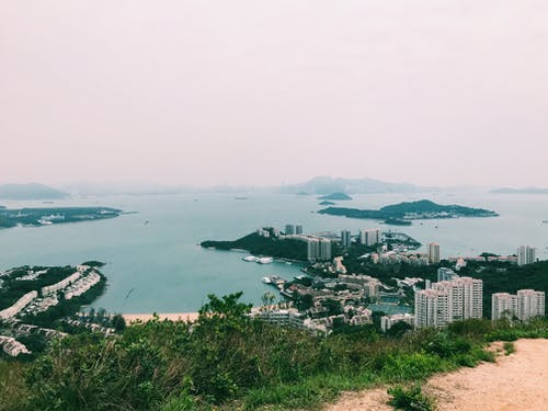 From above spectacular view of small islands and mounts surrounded by sea and sandy coast with modern multistage houses and growing grass on foggy day under white sky