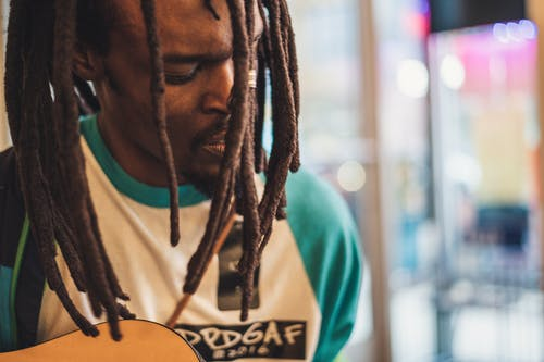 Crop stylish black musician singing song while playing guitar indoors