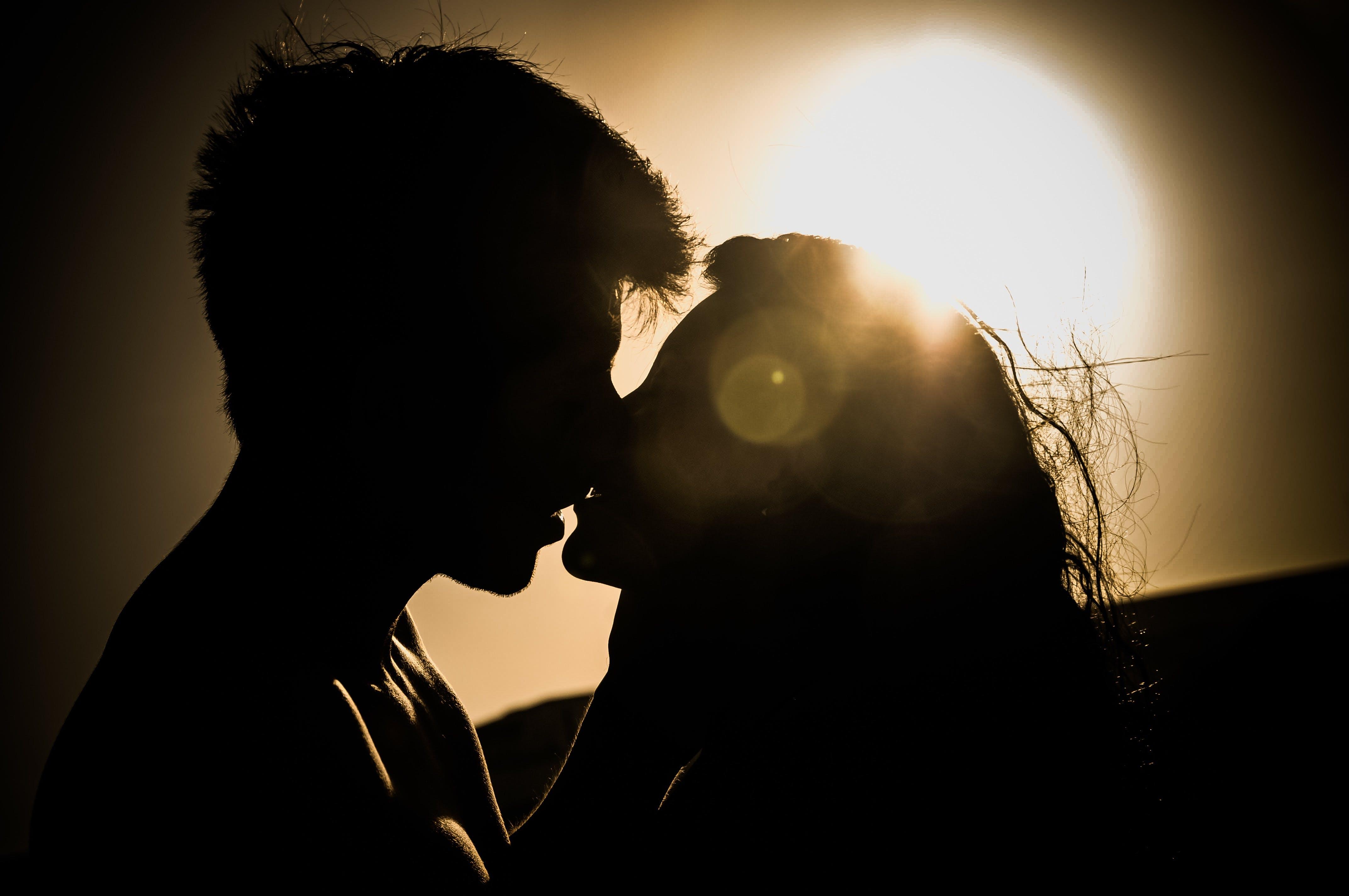 Silhouettes of Couple Kissing Against Sunset