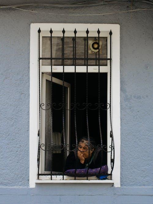 Thoughtful senior Hispanic woman leaning on hand on windowsill