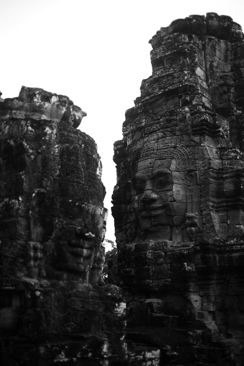 Amazing scenery of massive rough rocky cliffs with carved faces on slopes located in Angkor Thom Cambodia