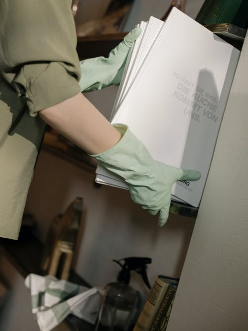 Person in Green Scrub Suit Holding White Printer Paper