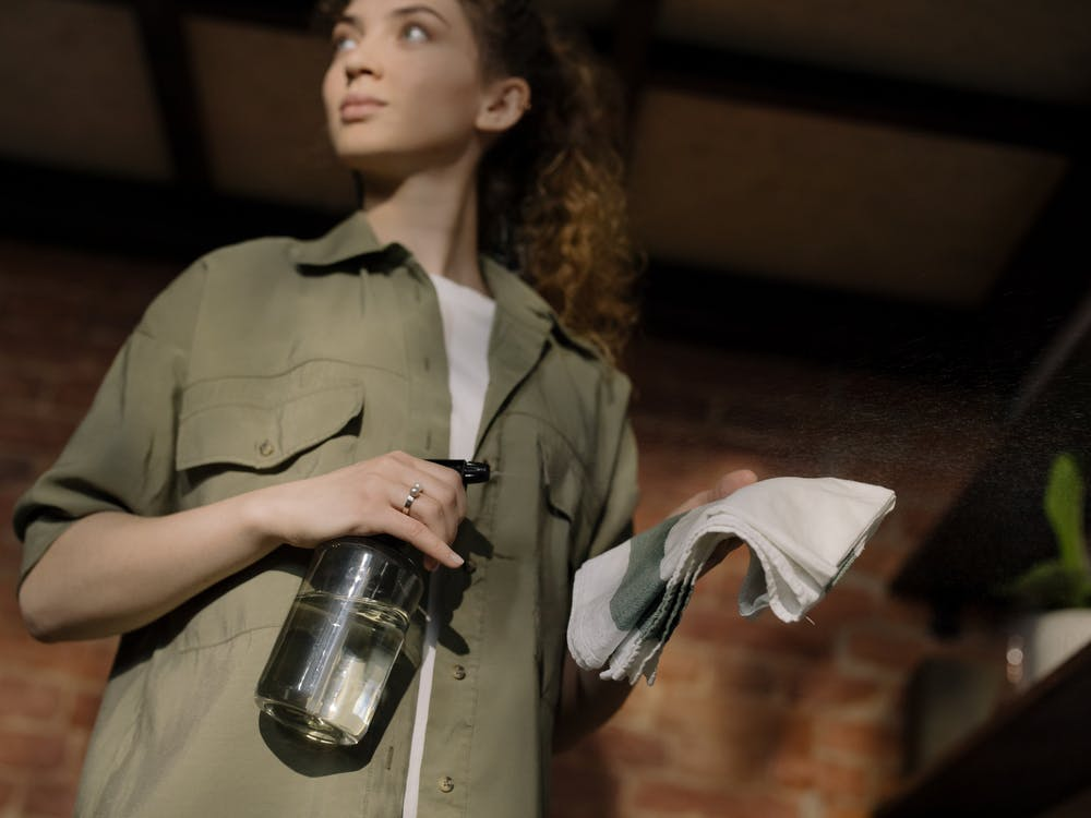 Woman in Green Button Up Shirt Holding Clear Glass Bottle