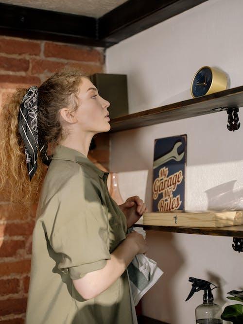 Woman in Green Long Sleeve Shirt Standing Beside Brown Wooden Shelf