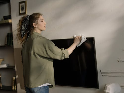 Woman in Gray Long Sleeve Shirt and Blue Denim Jeans Standing Near Black Flat Screen Tv