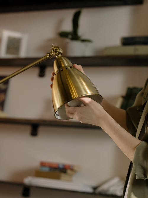 Person Holding Gold Round Pendant Lamp