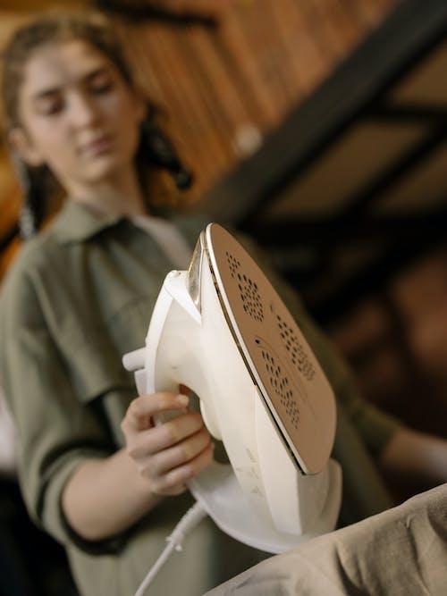 Woman in Gray Robe Holding White Ceramic Bowl