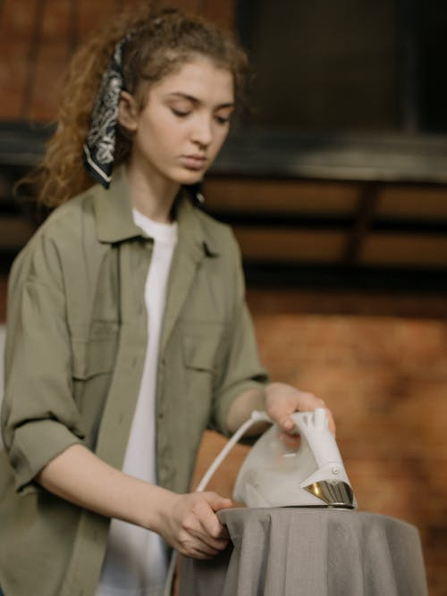 Woman in Gray Button Up Shirt Holding White and Gray Clothes Iron