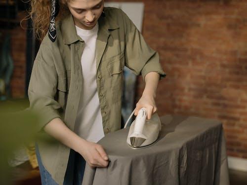 Woman in Brown Button Up Shirt Holding White Ceramic Mug