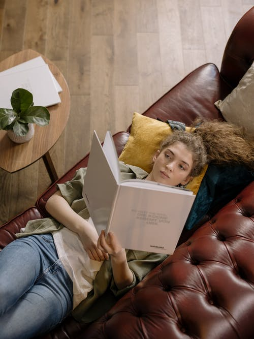 Woman in Blue Denim Jeans Sitting on Brown Leather Couch