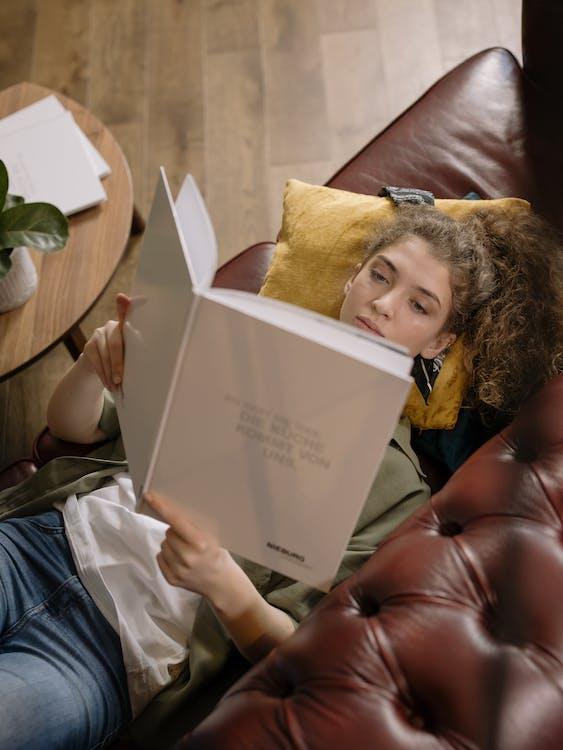 Girl in White Long Sleeve Shirt Reading Book