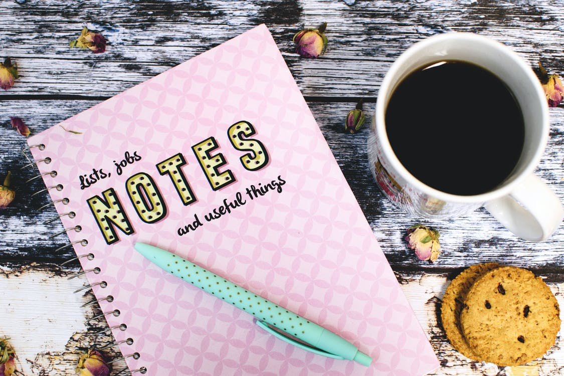 Pink Notebook Beside Cup of Coffee and Cookies