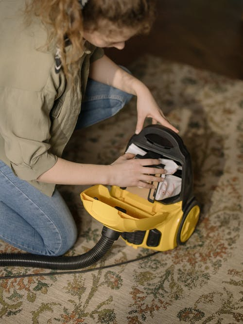 Woman in Brown Jacket and Blue Denim Jeans Sitting on Yellow and Black Vacuum Cleaner