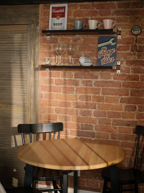 Brown Wooden Round Table Near Brown Brick Wall