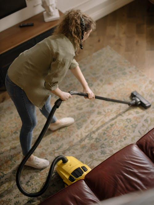 Woman in Beige Long Sleeve Shirt and Maroon Pants Holding Vacuum Cleaner