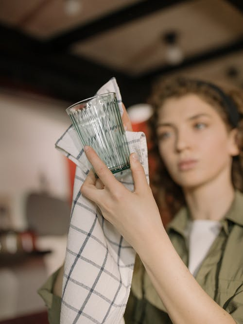 Woman in White and Black Plaid Shirt Holding Us Dollar Bill