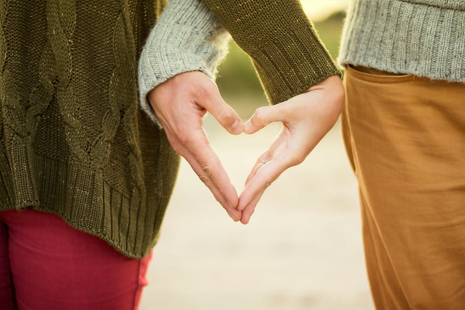 Selective Focus Photography Two Person Making Heart Hand Sign