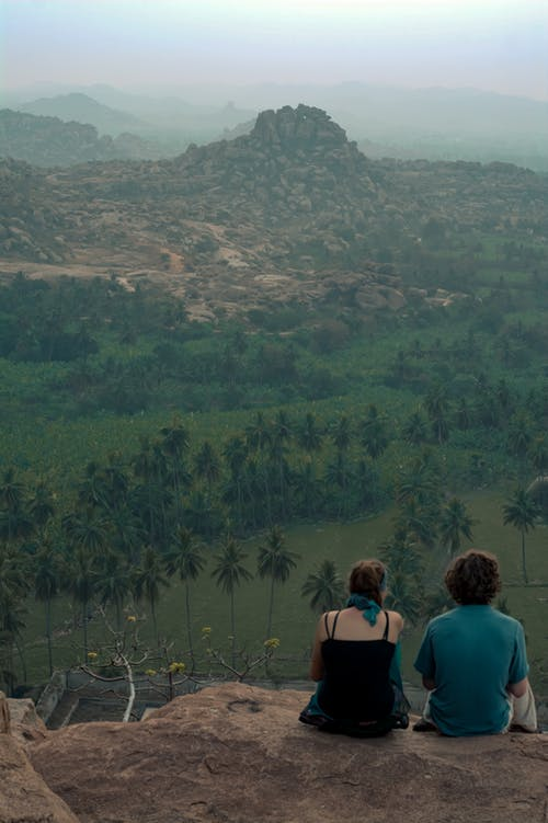 Back view full body faceless couple in casual wear resting on rough mountain top and enjoying spectacular scenery of green mountainous terrain
