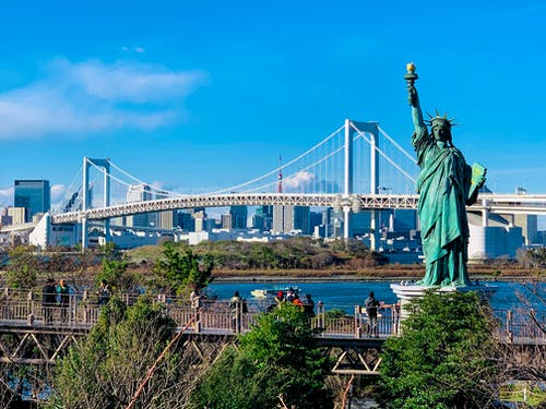 Replica of Statue of Liberty located in Tokyo against modern Rainbow Bridge and contemporary metropolis cityscape on clear sunny day