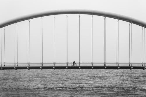 Grayscale Photography of Person Riding Bicycle on Concrete Bridge
