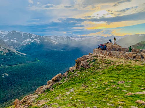 Anonymous travelers standing on stony observation point in Forest Canyon of Rocky Mountain National Park and admiring breathtaking view during sunset in Colorado