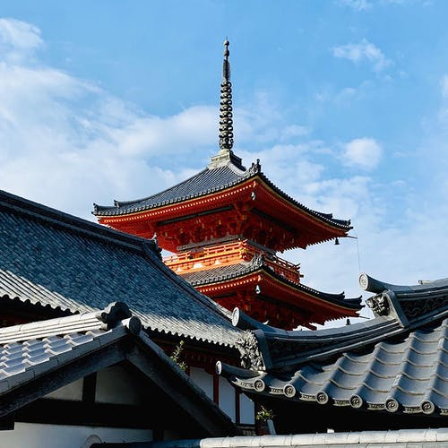 From below of ancient ornamental pagoda in Kiyomizu dera temple complex located in Kyoto against blue sky on sunny day