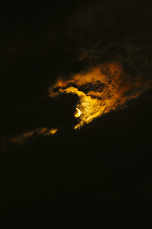 From below of bright full moon shining through thick clouds in dark night sky