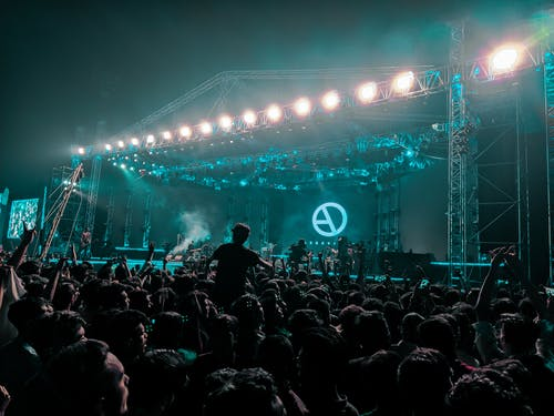 Back view crowd of anonymous people dancing and clapping during outdoor live rock festival at night