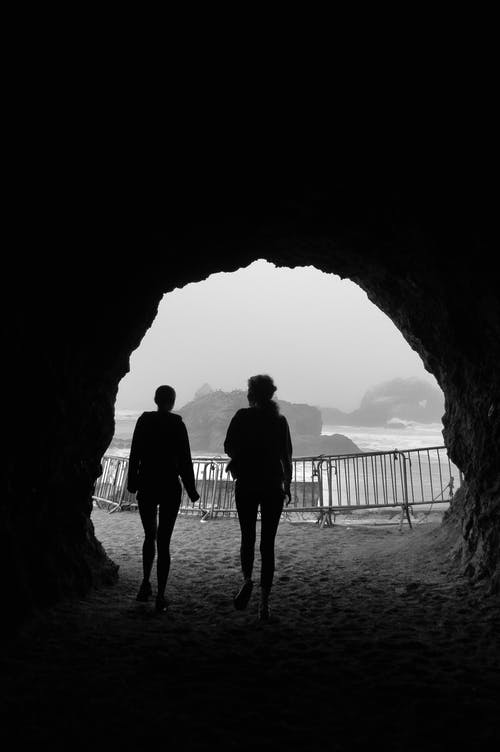 Silhouettes of anonymous women walking along rocky tunnel at seaside