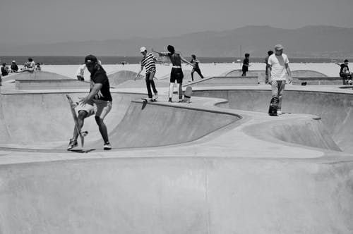 Skateboarders riding in skate park on summer day