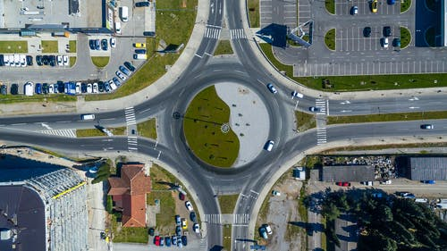 Drone view of roundabout at intersection of asphalt roads near modern buildings and parked cars in city district on sunny day