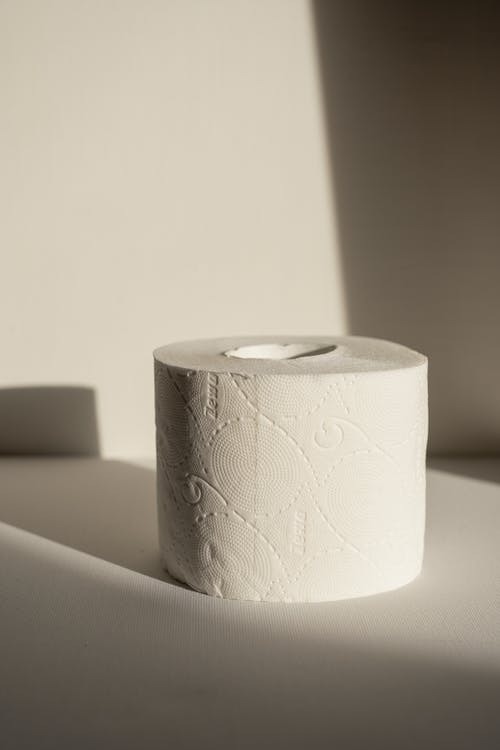 Close-Up Shot of a Tissue Paper Roll on a White Surface