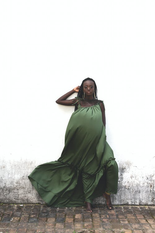 Woman in Green Dress Standing Beside A White Wall