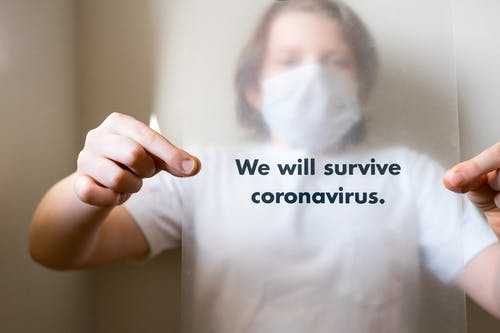 Man in White Crew Neck T-shirt Holding A Slogan On Coronavirus