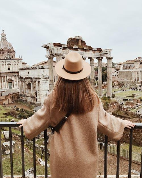 Woman in Beige Sun Hat Standing on Balcony