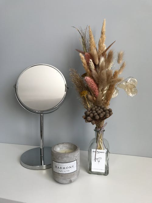 Dried Flowers in Clear Glass Vase  Wiith Mirror And Scented Candle On Display
