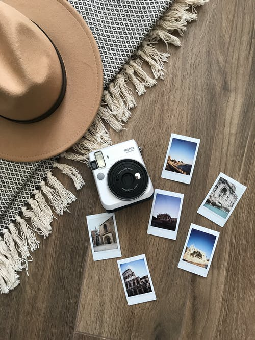 Instant Photos And Camera On Wooden Floor With Concept Of Travel