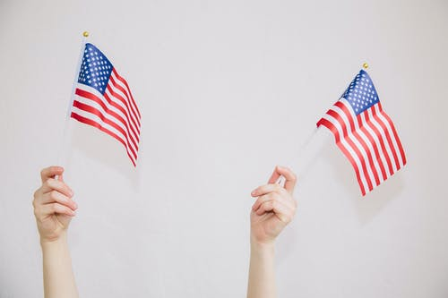 Unrecognizable woman with American flags in hands