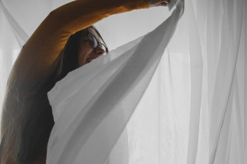 Cheerful young lady having fun in bedroom while hiding behind curtains