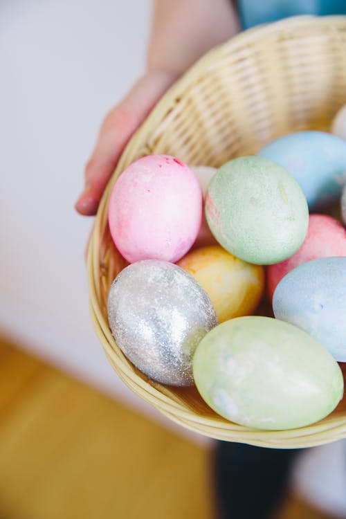 Person Holding a Woven Basket Full of Easter Eggs