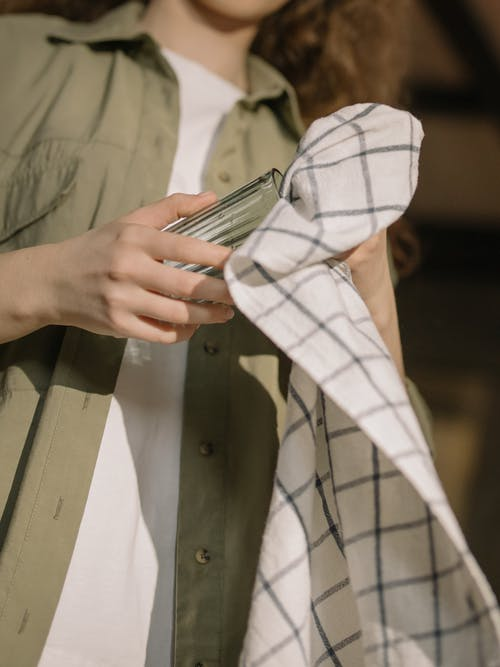 Person in White and Black Plaid Button Up Shirt Holding Black Smartphone