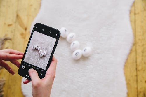 Person Holding Iphone Taking Photo of White Round Balls