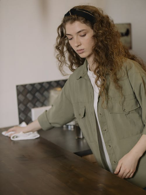 Woman in Gray Button Up Long Sleeve Shirt Sitting by the Table