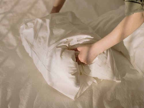 Person Holding White Textile on White Bed